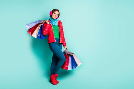 Full body photo of positive girl tourist hold many bags she buy on autumn fall weekend wear green jumper red season wear shoes pink blue pants trousers isolated turquoise color background