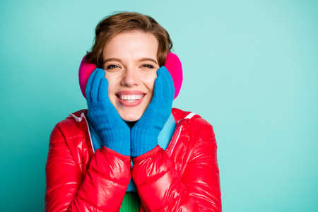 Closeup photo of funny lady holding hands on cheekbones excited christmas holiday emotions wear casual red overcoat gloves scarf pink ear covers isolated teal color background