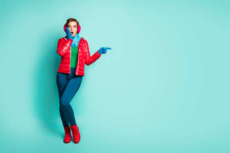 Full body photo of pretty lady indicate fingers empty space showing sale prices hand on cheek wear red overcoat blue scarf pink ear muffs pants shoes isolated teal color background