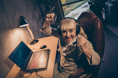 Portrait of her she nice attractive cheerful cheery satisfied gray-haired blonde grandma playing game contest battle championship win great success at industrial loft modern concrete style interior 版權商用圖片
