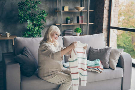 Profile photo of amazing white haired aged granny holding tidy pullover hands put it in stack spring general cleaning house sitting divan living room indoors