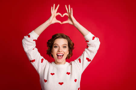 Portrait of funny cheerful positive passionate girlfriend make hands fingers heart enjoy 14-february celebration wear stylish sweater over bright color background