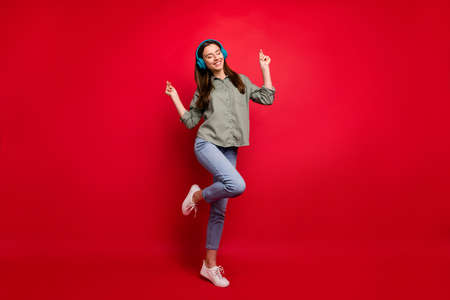 Full length photo of pretty lady using modern technology headphones on ears listen new popular youth song dj wear casual grey green shirt jeans isolated red color background