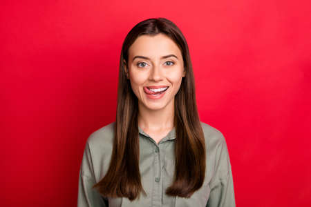 Close-up portrait of her she nice attractive lovely cheerful cheery straight-haired girl wearing khaki shirt licking lips flirting isolated over bright vivid shine vibrant red color background