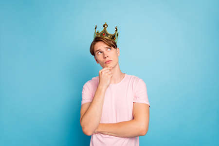 Portrait of pensive guy prince have gold crown think thoughts feel unsure about his coronation touch chin look copyspace wear modern clothes isolated over vivid background