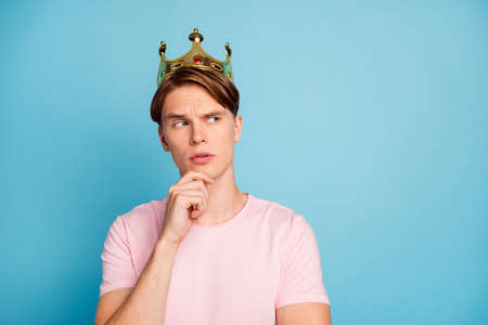 Portrait of minded pensive guy have golden tiara imagine he kind think thoughts choice decision touch hand chin wear good looking outfit isolated over blue color background Banco de Imagens