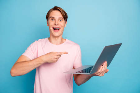 Look summer discounts. Excited impressed guy hold computer find incredible online bargains point index finger laptop screen scream wear good look clothes isolated blue color background