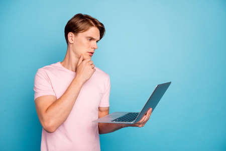Profile side photo of focused university student guy study learn use computer think project decide decision chose choice solution wear stylish pink t-shirt isolated blue color background
