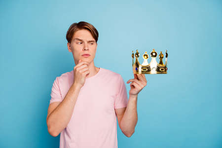 Portrait on minded pensive guy hold golden crown think thoughts about his king coronation decision touch chin hand wear good looking outfit isolated over blue color background Banco de Imagens