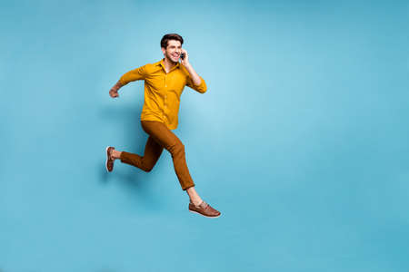 I'm on my way. Full length photo of crazy guy jumping high rushing to party holding, telephone speaking friends wear yellow shirt pants isolated blue color background