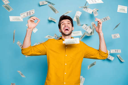 Photo of screaming excited emotional guy having, won jackpot in lottery smiling toothily isolated over blue pastel color background in yellow shirt