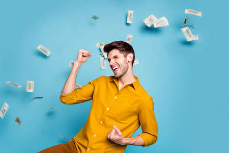 Photo of excited ecstatic crazy shouting manager having received salary payment, wearing yellow shirt saying yes isolated over pastel color blue background