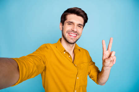 Self-portrait of his he nice attractive cheerful cheery positive content, brown-haired guy showing v-sign isolated on bright vivid shine vibrant blue green turquoise color background