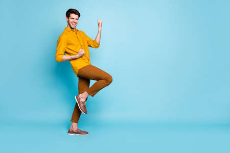 Full length body size photo of cheerful excited crazy rejoicing man in footwear, sneakers screaming encouraged near empty space isolated over pastel color background