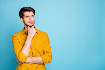 Photo of freelancer guy seriously looking side empty space holding arm on chin thinking over startup creative idea wear yellow shirt isolated blue color background