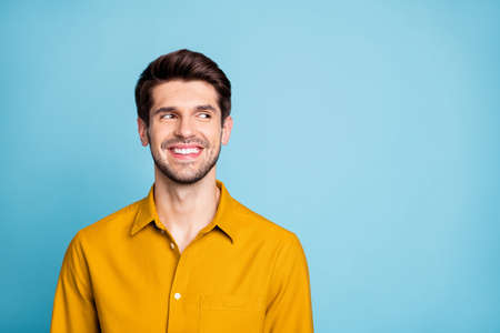 Photo of cheerful nice creative young guy freelancer in yellow shirt looking into empty space smiling toothily isolated over blue pastel color background
