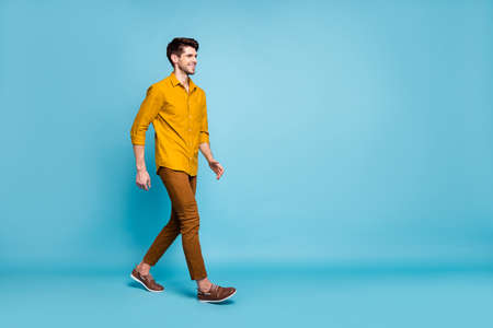 Turned full length body size photo of attractive man going towards his workplace wearing shoes smiling toothily beaming isolated over blue pastel color background