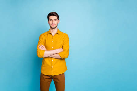 Photo of strict serious man with arms crossed looking at you intently near empty space isolated over blue pastel color background