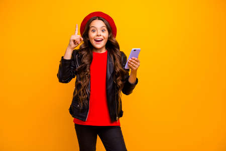 Portrait of her she nice attractive trendy cheerful cheery long-haired girl wearing streetstyle using cell creating smm isolated over bright vivid shine vibrant yellow color background