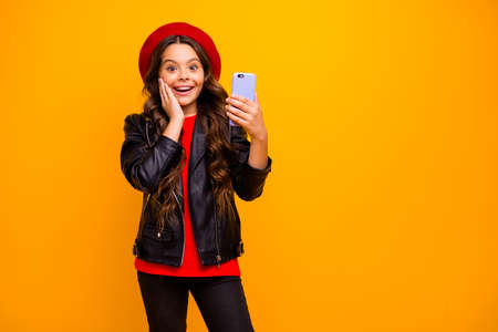 Portrait of her she nice attractive delighted cheerful excited long-haired girl wearing streetstyle using cell modern digital technology isolated over bright vivid shine vibrant yellow color background
