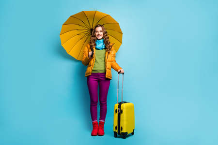 Full length photo of pretty traveler lady hold umbrella rolling bag suitcase wait airport journey wear yellow overcoat blue scarf violet trousers boots isolated blue color background