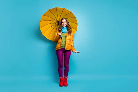 Full body photo of funny pretty lady hold bright umbrella enjoy spring sunny day walk street abroad wear yellow overcoat scarf violet trousers red shoes isolated blue color background Imagens