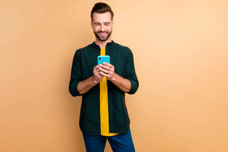 Photo of nice handsome hipster guy holding telephone hands good mood texting with friends speak over weekend meeting wear casual outfit isolated beige color background Stock Photo