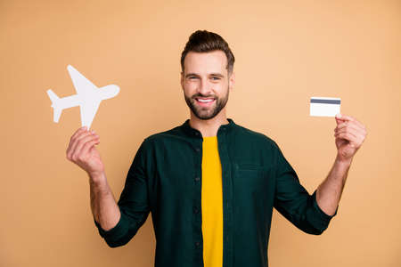 Honey, its vacation time. Photo of nice hipster guy holding credit card paper air plane demonstrating girlfriend good news wear casual outfit isolated beige color background