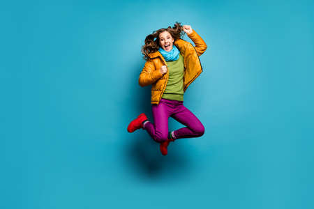 Full body photo of pretty lady jump high up celebrating amazing achievement wear casual yellow overcoat scarf violet pants red boots green pullover isolated blue color background 版權商用圖片