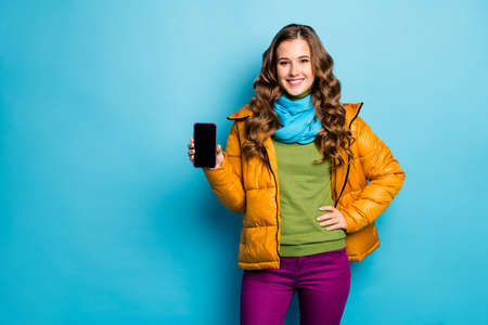 Photo of pretty lady hold telephone hands advising new gadget smart phone model low sale price wear yellow overcoat scarf violet trousers green jumper isolated blue color background