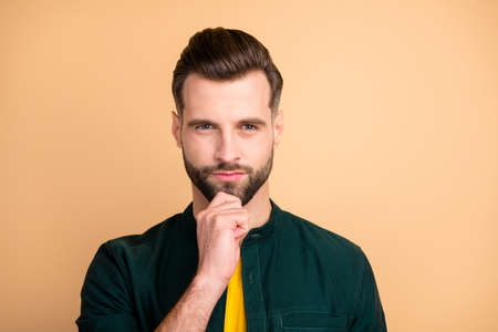 Closeup photo of handsome guy holding hand on chin deep thinking unsure startup idea is ready for presentation corporate meeting wear casual outfit isolated beige color background Banco de Imagens