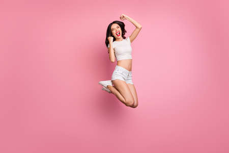 Full length body size view of her she nice attractive lovely cheerful cheery crazy wavy-haired girl jumping having fun celebrating attainment isolated over pink pastel color background
