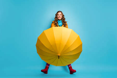 I dont need it. Full length photo of pretty lady hold umbrella enjoy spring sunny day street wear yellow overcoat blue scarf trousers red boots isolated blue color background