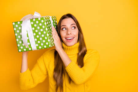 Interesting what is it. Amazed funky teen girl get big giftbox with white ribbon for anniversary she wait all life wear casual style jumper isolated over bright color background Reklamní fotografie