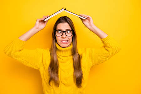 Funky funny foolish nerd girl have high school rest relax put book above head grimace wear stylish sweater isolated over bright shine color background Stok Fotoğraf - 137871934