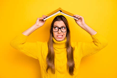 Portrait of frustrated afraid girl high school girl hold book above head look feel fear about academic graduation test exam wear trendy pullover isolated over yellow color background Stok Fotoğraf - 137872778