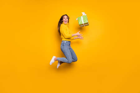 Full body profile side photo of amazed funky girl jump throw gift box she get receive on 14-february celebration party jump wear collar knitted sweater isolated bright color background Stock fotó