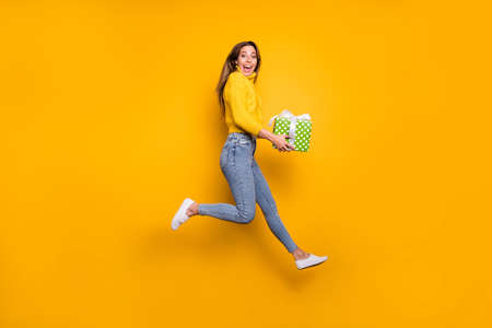 Full length profile side photo of amazed crazy funky girl like holiday sales hold green dotted gift box bring boyfriend jump run wear casual style clothing isolated yellow color background