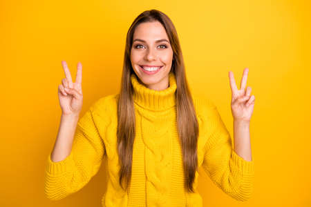 Portrait of positive cheerful girl have winter weekends make v-sign enjoy free time wear soft warm clothing isolated over bright color background