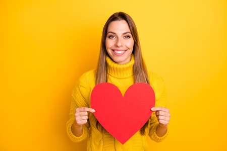Portrait of cheerful positive youth passionate girlfriend celebrate 14-february date with her boyfriend get red big paper card heart wear vivid jumper isolated over bright color background