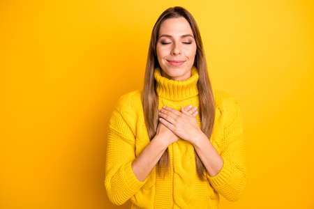 Portrait of calm peaceful positive girl feel grateful dreamy out hands on chest wear warm soft jumper isolated over bright color background