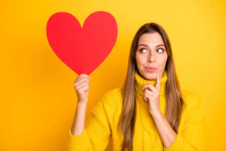 Portrait of minded girl get red big paper card heart from secret admirer think thoughts who he is wear knitted collar bright jumper isolated vibrant color background