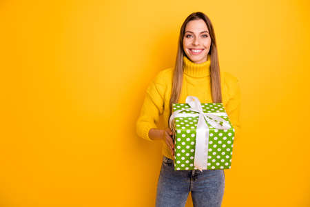 Portrait of cheerful positive girl celebrate christmas time party get big green white dotted present box feel content emotions wear knitted jumper denim jeans isolated shine color background Stock fotó