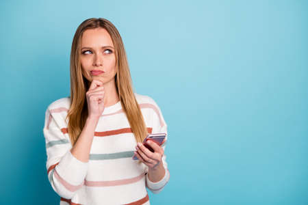 Photo of bewildered interested focused woman wearing striped sweater looking into empty space in search of creative ideas for presentation in her blog isolated pastel color background blue