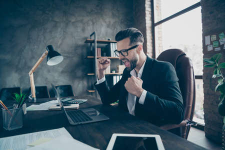 Profile photo of handsome business guy holding hands fists raised, celebrating success of new company project wear specs black blazer shirt suit sitting chair office indoors Фото со стока
