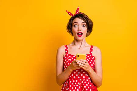 Porträt aufgeregt, erstauntes Mädchen, das Handy benutzt, unglaubliche soziale Netzwerkbenachrichtigung erhalten, beeindruckt schreien wow omg tragen roten Polka-Dot-Retro-Rock isoliert heller Glanzfarbhintergrund Standard-Bild