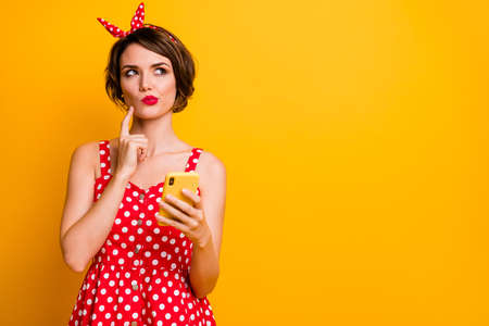 Portraut of minded pensive girl blogger want type post text chatting think thoughts look copyspace touch finger chin wear retro style outfit isolated over bright color background