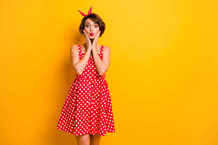 Photo of funny pretty lady hold arms on cheeks sending air kiss flirty mood wear retro summer dotted red white dress headband isolated bright yellow color background