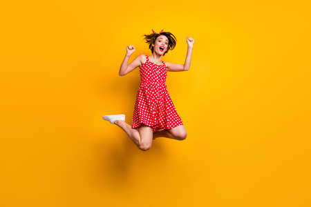 Full length photo of cheerful crazy ecstatic girl win lottery enjoy rejoice victory jump raise fists scream yes wear good look skirt sneakers isolated over bright color background