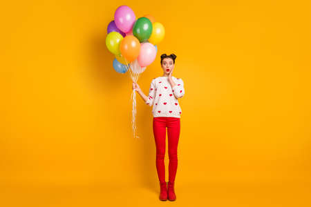 Full size photo of funny lady hold colorful air balloons open mouth unexpected surprise wear hearts pattern sweater red pants shoes isolated yellow color background
